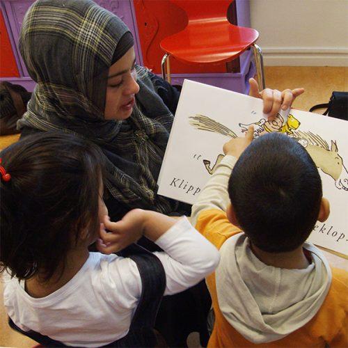 DOE Taalontwikkeling stimuleren foto moeder en kinderen lezen